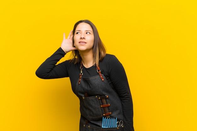 Kappersvrouw glimlachen, nieuwsgierig naar de zijkant kijkend, proberen te roddelen of een geheim afluisteren tegen een oranje achtergrond