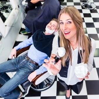 Kappersvrouw in haar salon met klanten