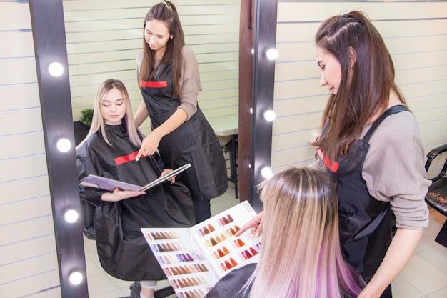 Kapperszaak. de kapper kiest haarkleur voor de klant van het meisje. selectie van haarverf in de catalogus. meisje in een schoonheidssalon, haarverzorging