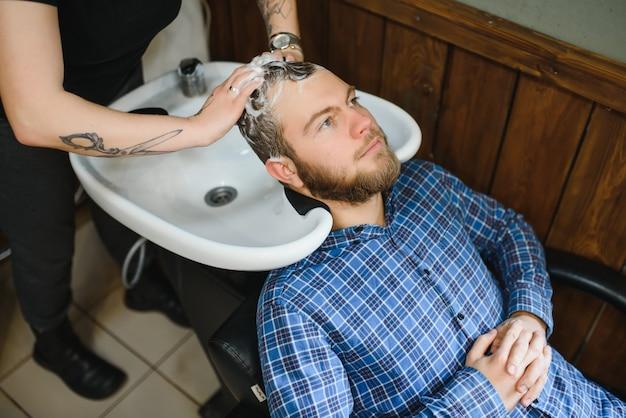 Kapperszaak. haarstylist wassen van het haar van de klant in de kapper