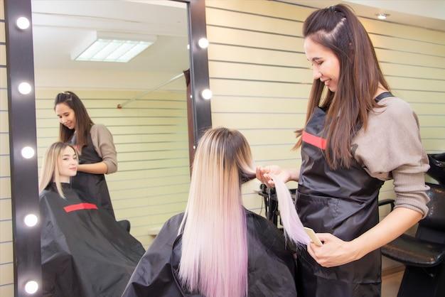 Kapperszaak. haarverzorging. kapper onderzoekt het haar van een vrouwelijke cliënt, voor kapsels en styling.