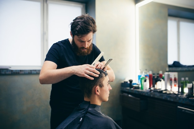 Kapperszaak. man knipt het haar van een andere man. maakt een kapsel