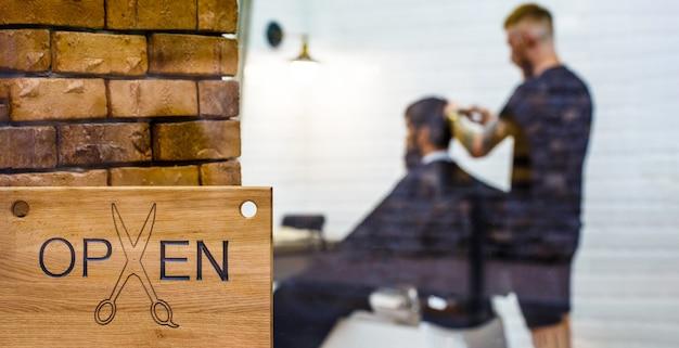 Kapperszaak. open kapperszaak. kapper of kapper. man een bezoekende haarstylist in de kapper.