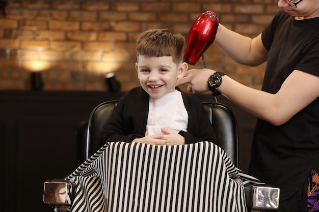 Kapperszaak. vrolijke jongen maakt een knipbeurt in de salon. kapper maakt kapsel voor een vrolijke jongen.