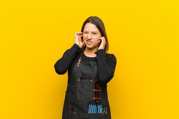 Kappervrouw die boos, gestrest en geërgerd kijkt, die beide oren bedekt met een oorverdovend geluid, geluid of luide muziek tegen een oranje achtergrond