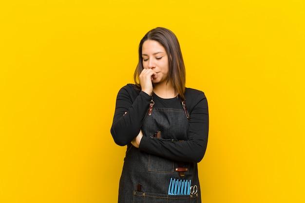 Kappervrouw die ernstig, nadenkend en bezorgd voelen, zijdelings starend met hand tegen kin tegen oranje muur wordt gedrukt die