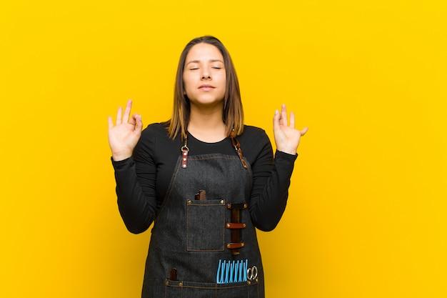 Kappervrouw die geconcentreerd en mediterend kijkt, tevreden en ontspannen voelt, denkt of een keus maakt tegen sinaasappel