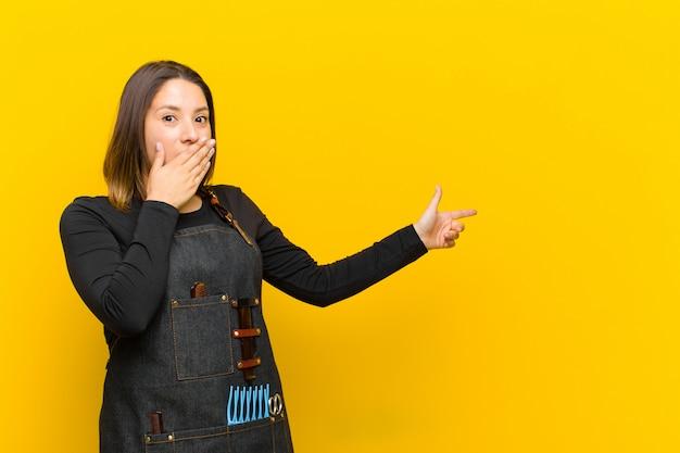 Kappervrouw die gelukkig, geschokt en verrast voelen, die mond behandelen met hand en naar zijexemplaarruimte richten tegen oranje achtergrond