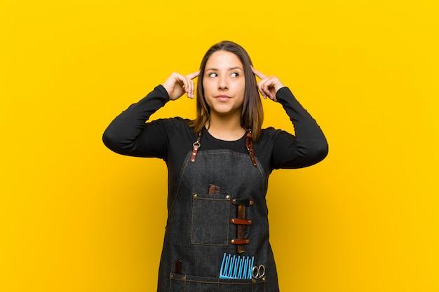 Kappervrouw die verward of twijfelen voelen, zich op een idee concentreren, hard denken, kijkend aan copyspace aan kant tegen sinaasappel
