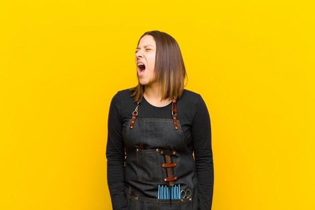 Kappervrouw die woedend gillen, agressief schreeuwen, gestrest en boos tegen oranje achtergrond kijken