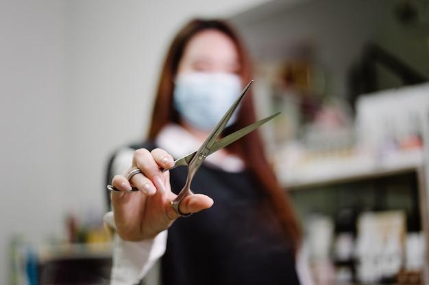 Kapsalon concept een mooie kapper poseren met een schaar in een hand in haar kapsalon omringd door haarverzorgingsproducten en apparatuur.