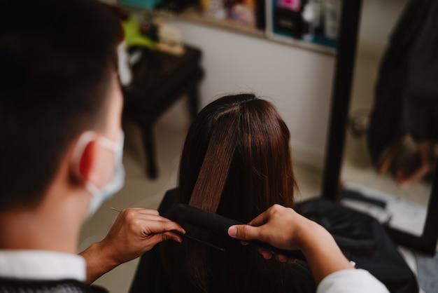 Kapsalonconcept een mannelijke haarstylist die met een stijltang werkt om het haar van een vrouwelijke klant recht te trekken.