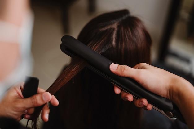 Kapsalonconcept een mannelijke herenkapper die met een stijltang werkt om het haar van een vrouwelijke cliënt recht te trekken.