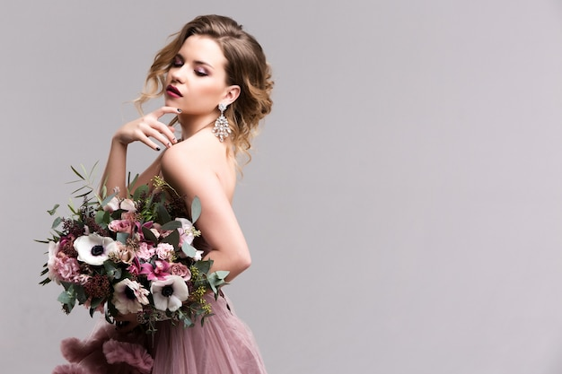 Kapsel. lang golvend haar. mode foto van jonge vrouw. sexy meisje poseren in roze jurk. studio.