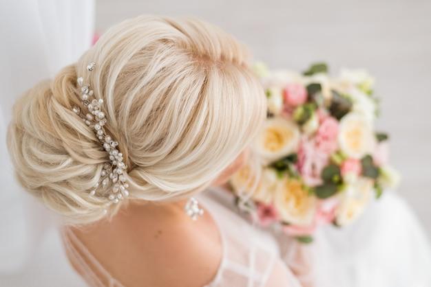 Kapsel van de bruid. een laag knotje op haar blonde haar. achter- en bovenaanzicht