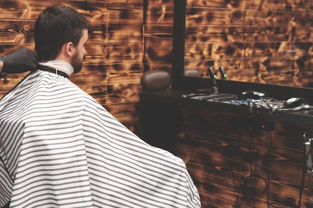 Kapselhoofd in herenkapper. kapper knipt haar op hoofd van cliënt. het proces van het creëren van kapsels voor mannen. kapperszaak.