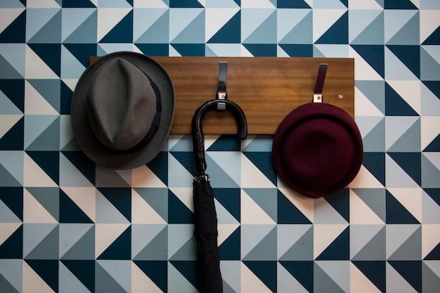 Kapstok met enkele hoeden en een paraplu op een blauwe driehoekenmuur