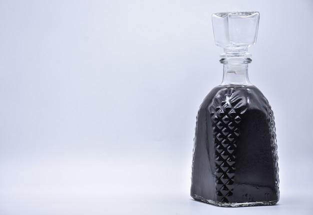 Karaf met zwarte vloeistof op wit wordt geïsoleerd