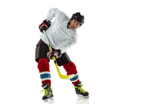 Karakter. jonge mannelijke hockeyspeler met de stok op ijsbaan en witte muur. sportman uitrusting dragen en helm oefenen. concept van sport, gezonde levensstijl, beweging, beweging, actie.