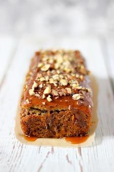 Karamel brownie taart met gehakte pinda's en noten erop