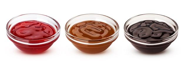 Karamel, chocolade sauzen en rode bessen jam in glazen kommen geïsoleerd op een witte achtergrond met uitknippad, verzameling van zoete toppings voor bakken en ijs