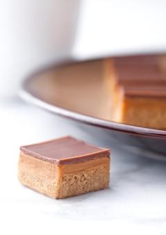 Karamel en koekjes shortcake bijt dessert op bruine plaat en koffiekop