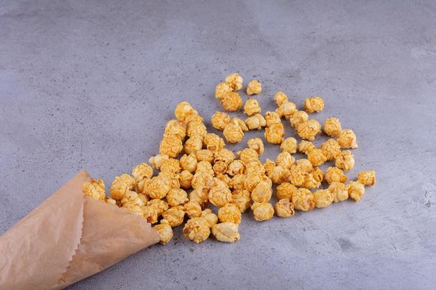 Karamel gearomatiseerde popcorn morst uit papierverpakking op marmeren achtergrond. hoge kwaliteit foto