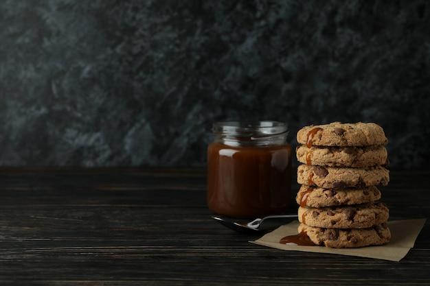 Karamel, lepel en koekjes op houten tafel