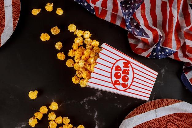 Karamel popcorn in gestreepte doos voor het kijken naar american football-wedstrijd op tv