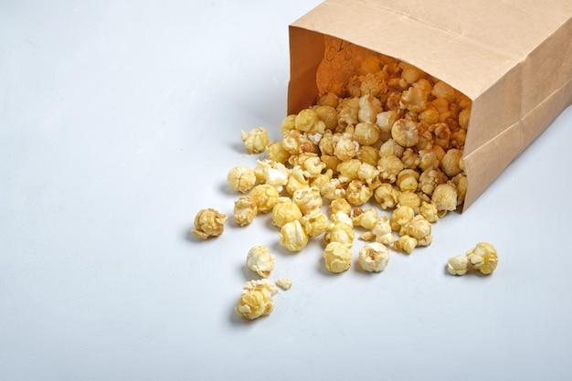 Karamel popcorn in papieren zak op grijze achtergrond