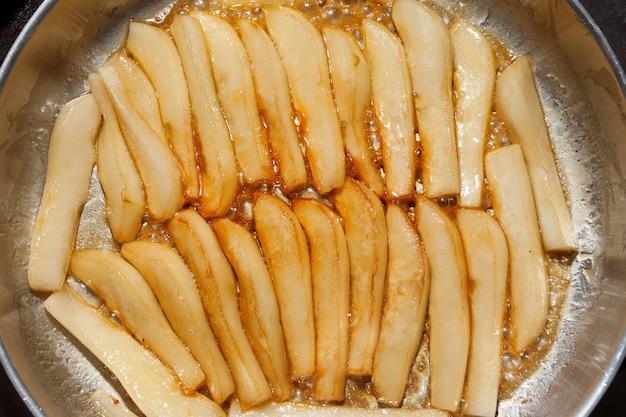Karamelisatie van peren in honingsiroop in pan.