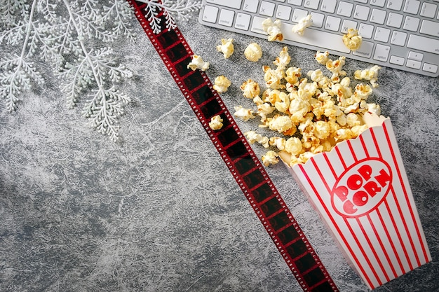 Karamelpopcorn in een papieren beker met toetsenbord op een loft-achtergrond 35 mm film plat gelegd bioscoop