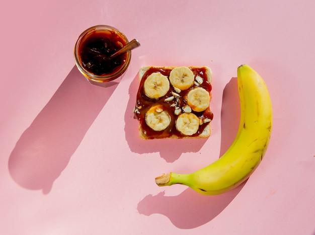 Karamelroom op brood met bananen op roze ondergrond. boven weergave