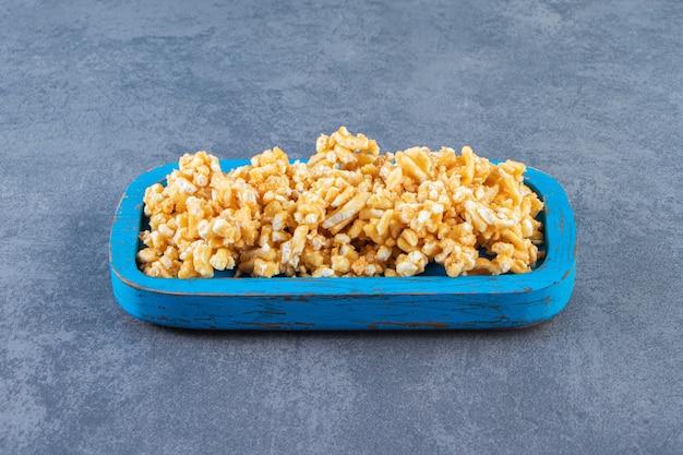 Karamelsnoepjes in een houten bord, op het marmeren oppervlak