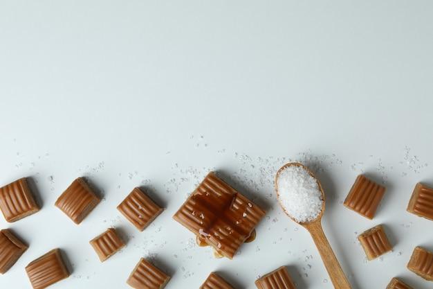 Karamelstukken en lepel zout op witte achtergrond