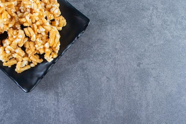 Karamelsuikergoed op een bord op het marmeren oppervlak