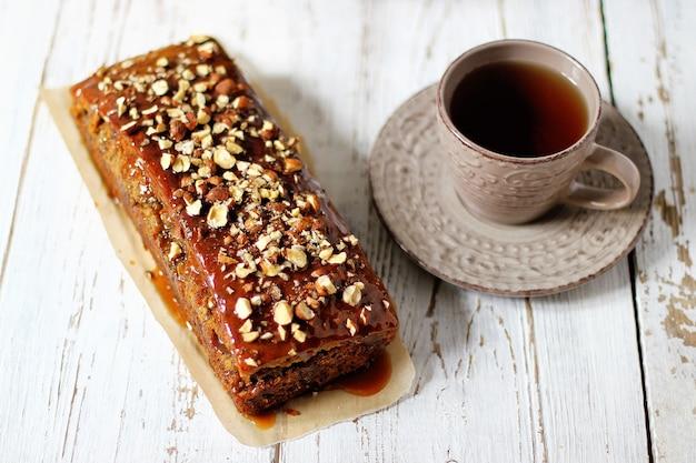 Karameltaartcake met gehakt noten en een kopje thee