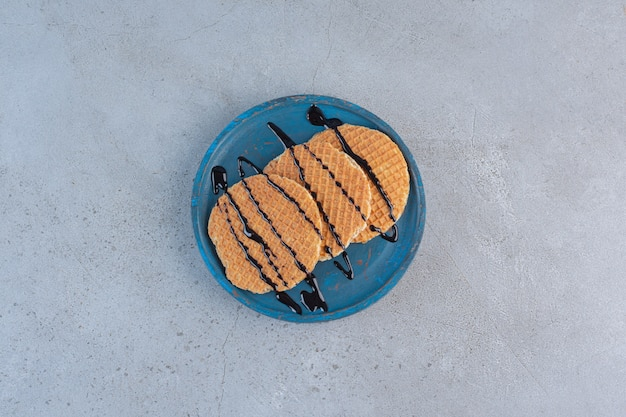 Karamelwafels versierd met chocoladesaus op blauw bord.