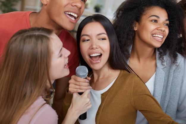 Karaoke-feestgroep van jonge en gelukkige multiculturele vrienden in vrijetijdskleding zingen met microfoon