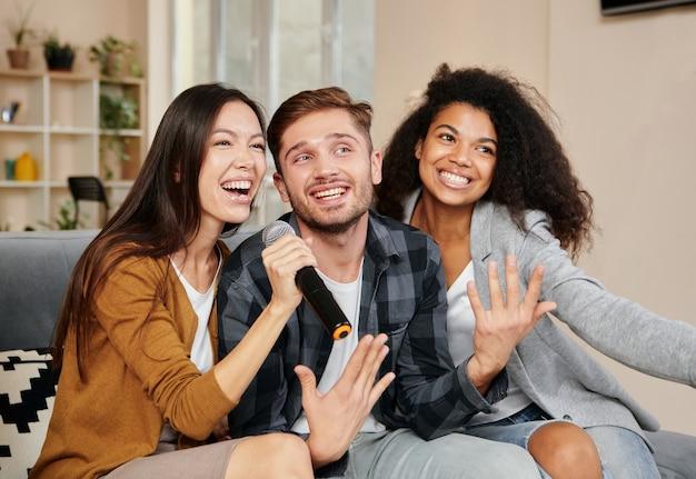Karaokezangers drie lachende vrienden die er gelukkig uitzien terwijl ze thuis karaoke spelen en zingen met