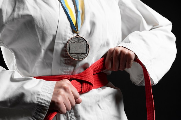 Karate atleet met rode riem en medaille