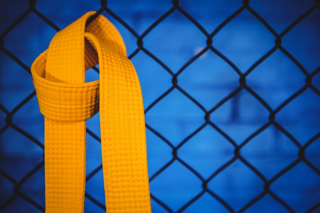 Karate gele riem opknoping op gaas hekwerk