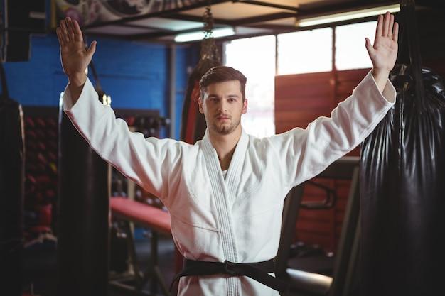 Karatespeler die zich met uitgespreide wapens bevindt