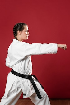 Karatevrouw in actie op rode achtergrond wordt geïsoleerd die