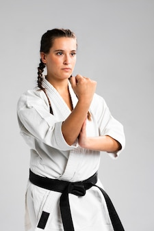 Karatevrouw in actie op witte achtergrond wordt geïsoleerd die