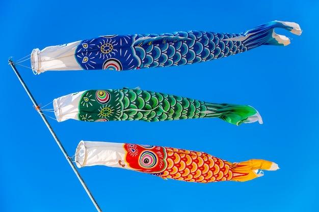 Karper-vormige kleurrijke windzakken tegen een strakblauwe lucht