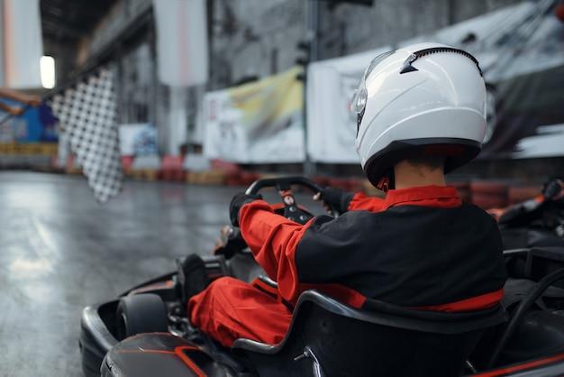 Kart racer in helm, achteraanzicht, karting autosport binnen. snelheidsrace op nauwe karrenbaan met bandenbarrière. snelle voertuigcompetitie, vrije tijd met veel adrenaline