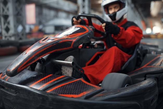 Kart-racer komt de bocht binnen, karting autosport indoor. snelheidsrace op nauwe karrenbaan met bandenbarrière. snelle voertuigcompetitie, vrije tijd met veel adrenaline