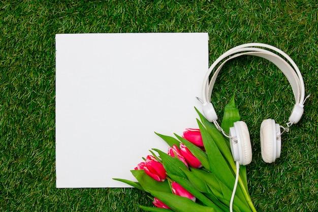 Karton en tulpen met koptelefoon op groen gras