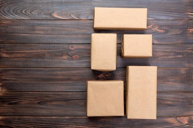 Kartondoos op de witte houten, bruine hoogste mening van het postpakket. copyspace